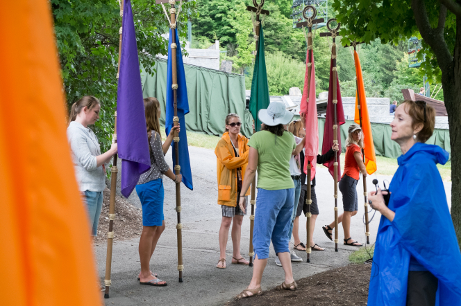 Young women from the Hill Cumorah Pageant line up holding flags on poles in a variety of colors, with two women directing them during rehearsal.