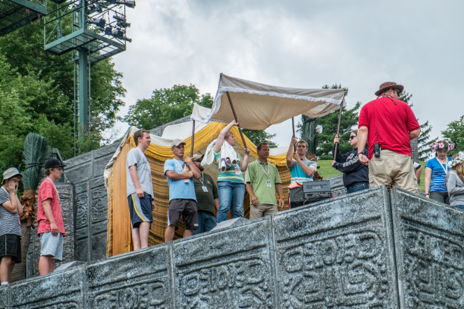 A large stage crew of men and women setting up a tent on the stage for the Hill Cumorah Pageant.