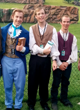 Three actors smiling and standing against a black wire fence with mountain props in the background at the Manti Pageant.