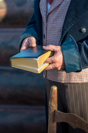 A close-up view of an actor from the Martin Harris Pageant standing and holding closed scriptures with his finger in the middle of the pages.