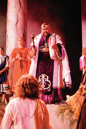 An actor with brown wavy hair standing in front of a king, who is wearing purple and white robes and holding a rod.