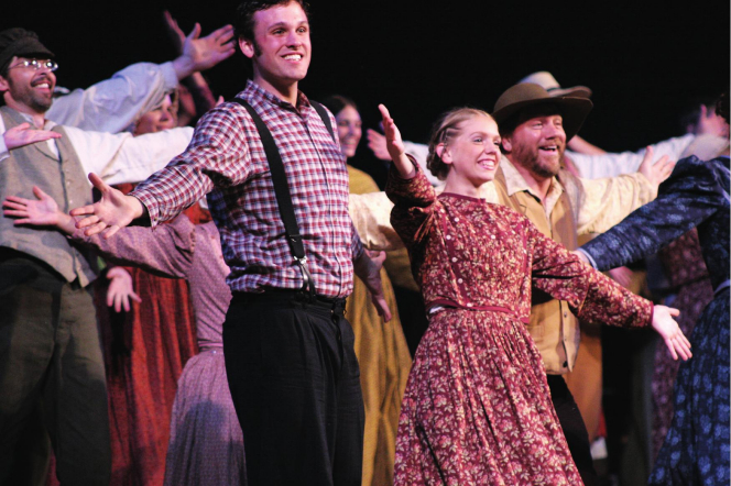 A group of actors and actresses from the Nauvoo Pageant standing with open arms and smiling.