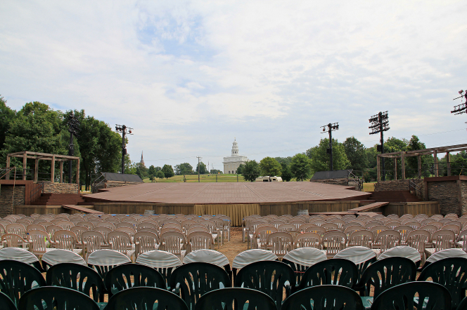 Rows of empty chairs and an empty stage at the Nauvoo Pageant, with the city of Nauvoo as a backdrop.