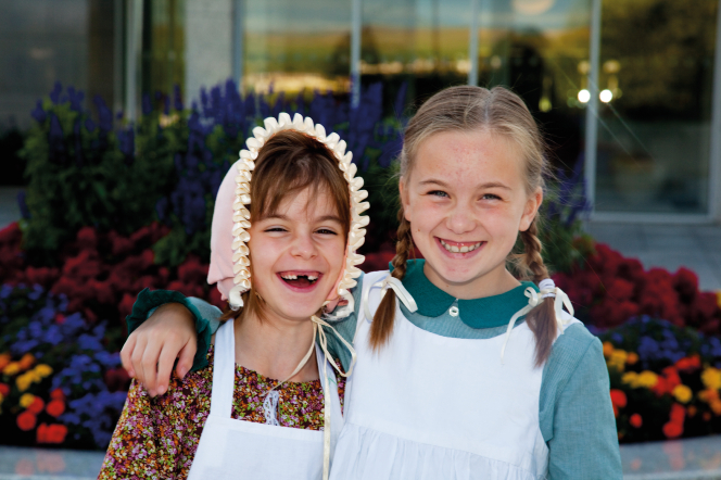 Two young actresses from the British Pageant, one wearing a bonnet and the other with two braids, standing in front of flowers and laughing.