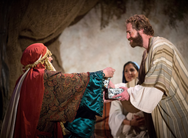 One of the Wise Men standing with outstretched arms and handing Joseph a gift while Mary stands in the background in the Arizona Christmas pageant.