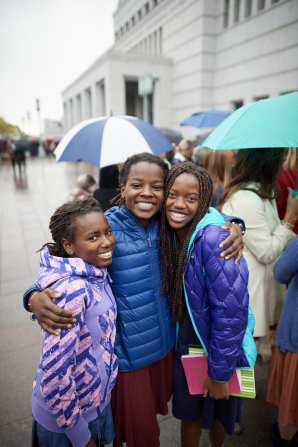 Three young women pose for a photograph outside of the Conference Center.