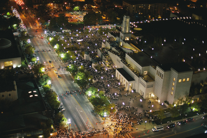 A night aerial view of the Conference Center with bright lights and with large groups of people gathered outside the building.