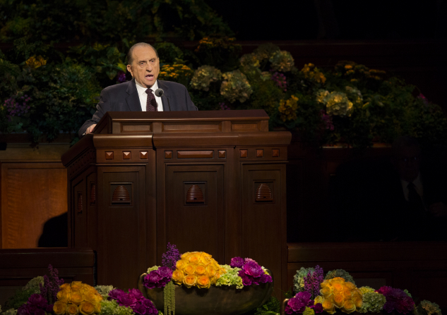President Monson standing at the pulpit, which is bordered with purple and yellow flowers, and speaking to the audience in general conference.