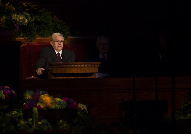 President Packer sitting in a red armchair while speaking at the pulpit in a session of general conference.