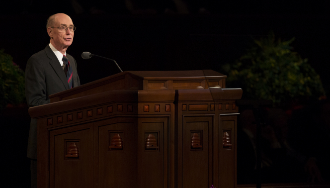 Henry B. Eyring standing behind the pulpit and speaking to the congregation in the Conference Center.