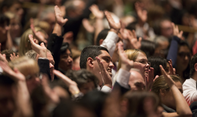 A man and woman in the congregation at general conference sustain Church leadership by raising their right arms.