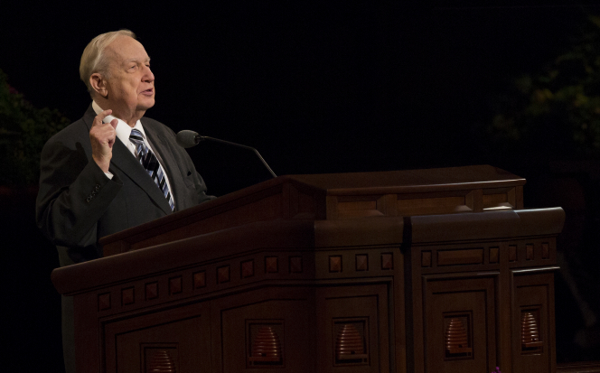 Elder Scott at the pulpit in the Conference Center, raising a finger while he speaks.