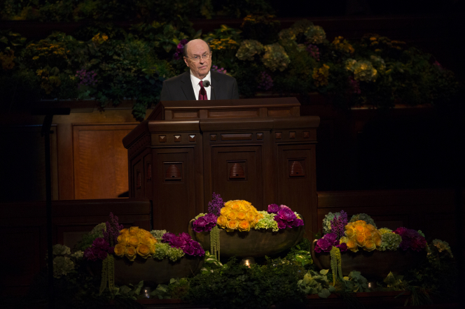 Elder Cook speaking to the audience while standing behind the pulpit during a session of general conference.