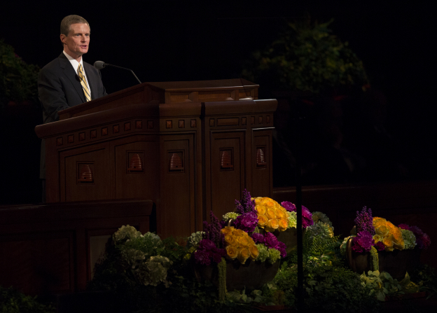 Elder Bednar in a yellow tie and black suit, standing at the pulpit and speaking at general conference.