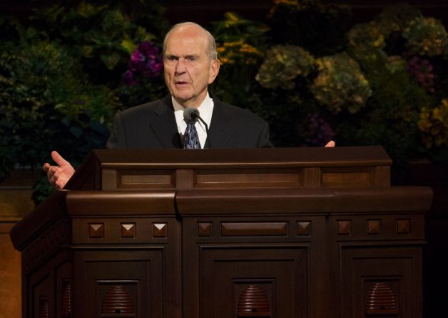 Elder Nelson standing with arms and hands slightly outstretched as he speaks behind the pulpit in general conference.