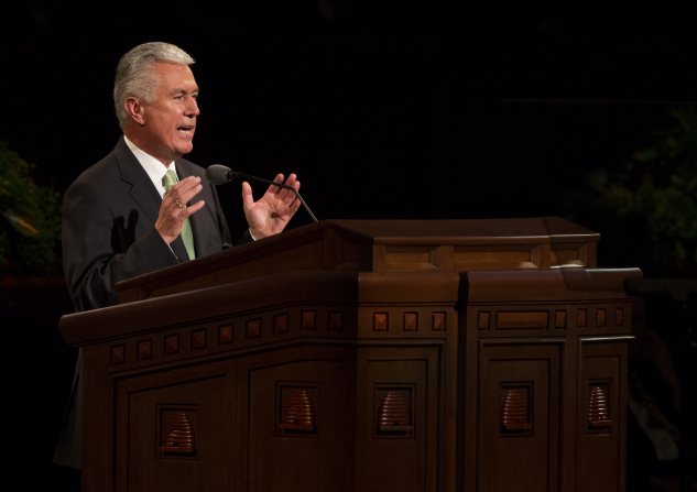 President Uchtdorf in a light green tie and black suit, standing and speaking to the audience in general conference.
