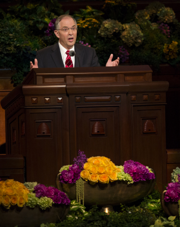 Neil L. Andersen in a red tie and black suit, speaking with his hands outstretched to the congregation in general conference.