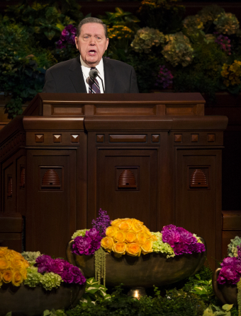 Elder Holland in a striped tie and black suit, standing and speaking behind the pulpit in general conference.