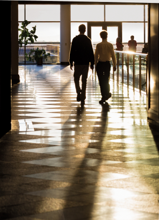 Two young men walking inside the Conference Center with sunlight streaming through the windows and lighting the room.
