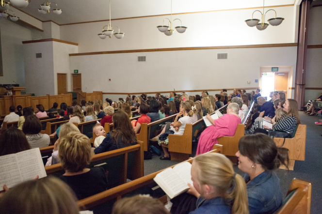 Women sitting in the pews at their local stake center, watching the broadcast of the general women's session.