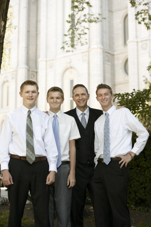 A man in a black suit standing beside three young men in white shirts and ties outside the temple, waiting for a session of general conference.