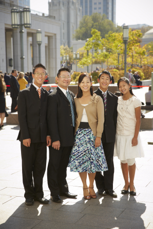 A father and mother stand beside their two sons in suits and their younger daughter while they wait outside the Conference Center.