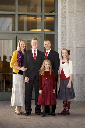 A father and mother standing and smiling with their tall son and two young daughters outside the Conference Center doors.