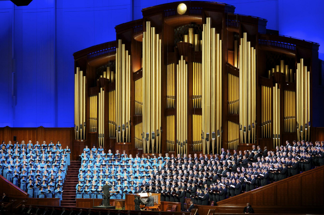 Women in turquoise dresses and men in black suits standing and singing during a session of general conference.