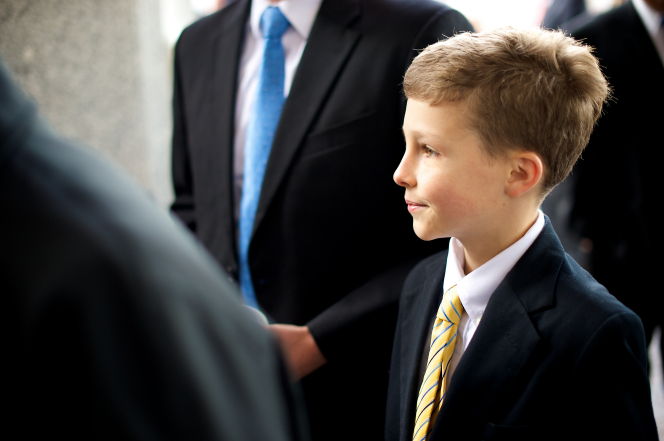 A boy in a white shirt, yellow tie, and black suit stands near a group of men outside of the Conference Center before a session of general conference.
