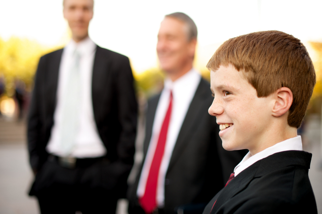 A young man in a white shirt, red tie, and black suit stands outside of the Conference Center near other men before a session of general conference.