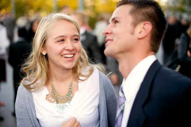 A smiling young woman in a white shirt standing near a young man in a suit outside of the Conference Center in downtown Salt Lake City.