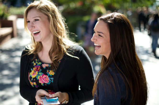 A woman with long brown hair laughs with another woman in a floral blouse as they stand outside of the Conference Center.