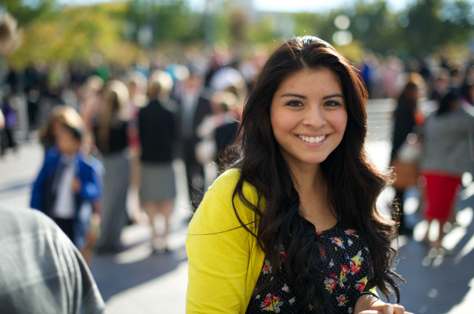 A woman with long dark hair and a bright yellow cardigan, standing outside of the Conference Center and smiling.