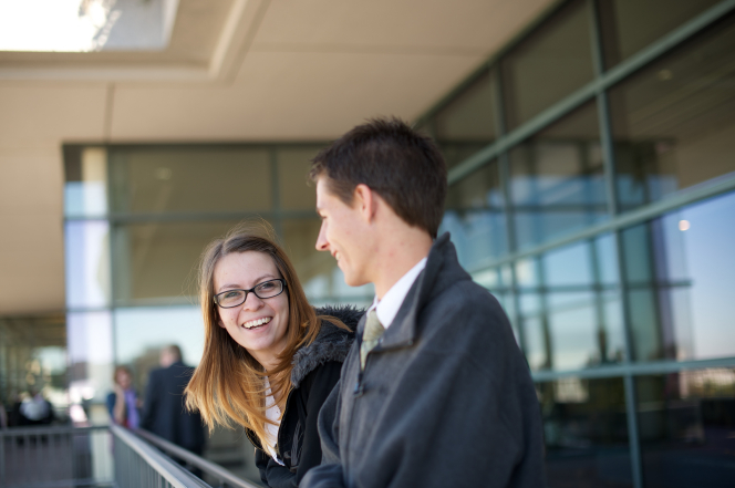 A man in a lightweight jacket stands near a woman wearing glasses as they smile and wait for a session of general conference.