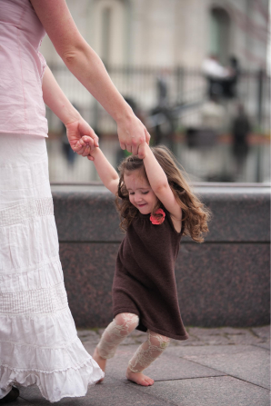 A mother in a long white skirt holding the hands of her daughter, who is dancing and smiling by the water fountain at Temple Square.