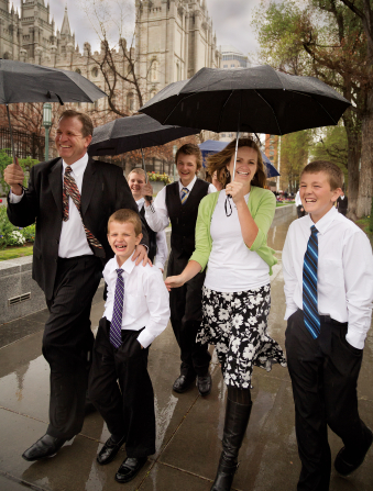 A father, mother, and their four sons smile while holding umbrellas as they walk through rain to the Conference Center.