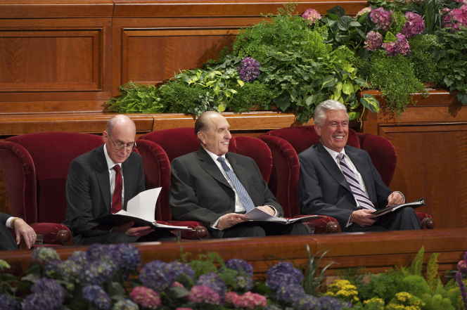 The members of the First Presidency in red armchairs, smiling and holding black binders during general conference.
