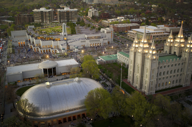 An aerial view at dusk of the temple, visitors' center, Tabernacle, and Conference Center on Temple Square.