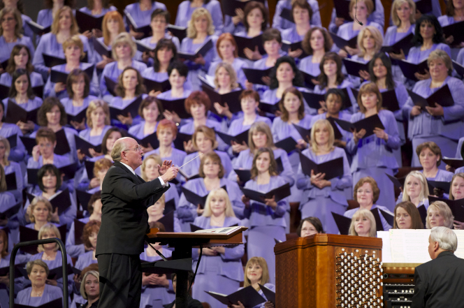 The Mormon Tabernacle Choir conductor standing and leading the music with his baton while women in the choir stand to the side.