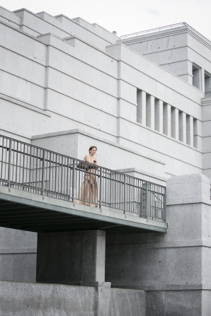 A woman in a long, light pink dress standing by the rail on the Conference Center balcony.