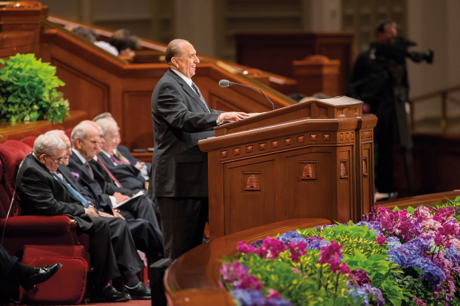 President Monson laughing behind the pulpit, with six Apostles sitting behind him during general conference.