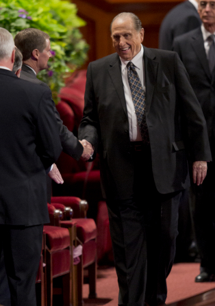 President Monson smiling and shaking an Apostle's hand inside the Conference Center.