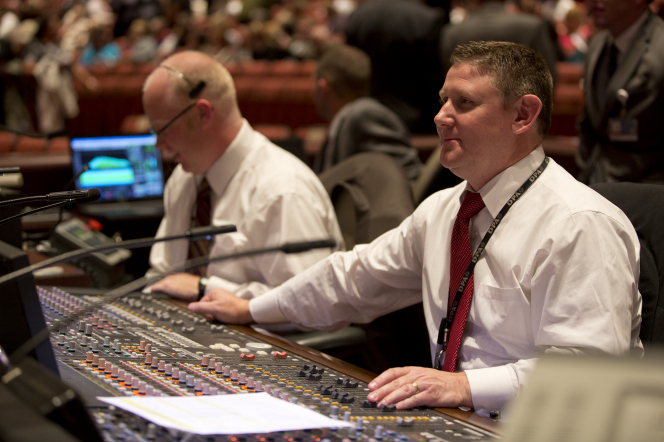 Two men in white shirts and red ties working for the technical crew behind the scenes at general conference.