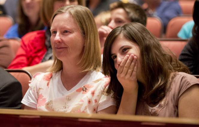 A mother with blond hair sitting beside her surprised daughter in the audience at the Conference Center.