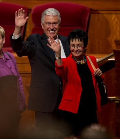 President Uchtdorf in a black suit and Sister Uchtdorf in a red blazer, standing and waving to the audience in the Conference Center.