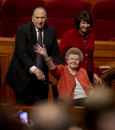 President Monson exits the Conference Center platform, pushing his wife in her wheelchair and walking alongside his daughter.