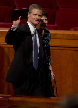 Elder Bednar waving with a journal in his hand as he exits the Conference Center with his wife.
