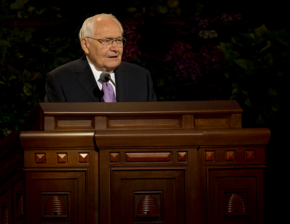 Elder Perry standing behind the wooden pulpit while speaking to the audience at general conference.