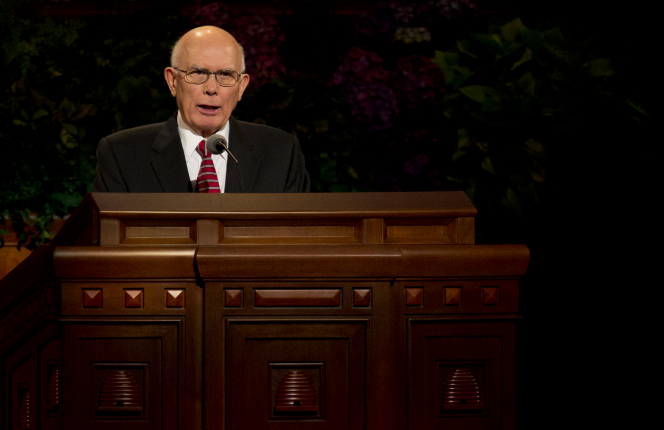 Elder Oaks standing behind the wooden pulpit in the Conference Center while addressing the audience.