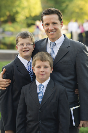 A father and his two sons in black suits and blue ties, standing outside before a session of general conference.